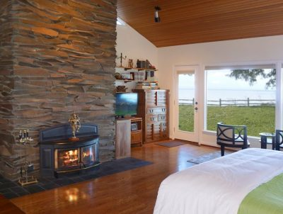 Hoh Rainforest Suite bedroom with a stone fireplace and a beautiful view
