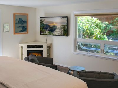 Cape Falttery Cottage bedroom with corner fireplace and large window