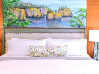 Cape Falttery Cottage bed with paintings over bed