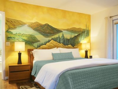 Lake Crescent Suite bedroom with murial on wall behind bed