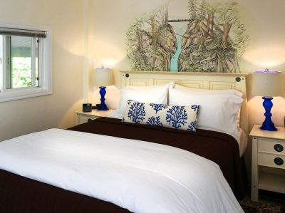 Sol Duc Falls Cottage bedroom with brown bedspread and artwork on wall