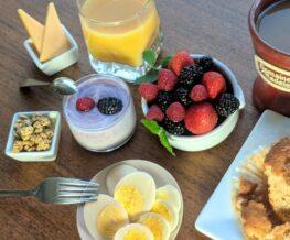 eggs, cheese, fruit, yogurt, granola, juice, muffin