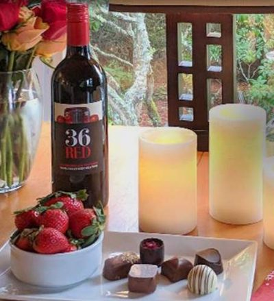Wine, strawberries, chocolate candy, candles and flowers