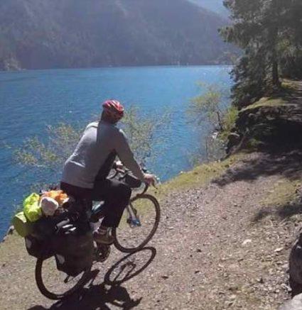 person biking along water's edge