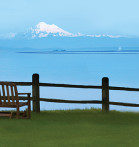 bench next to fence looking out over water and mountains in distance