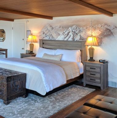 Hurricane Ridge bedroom with murial behind bed and wood-beamed ceiling